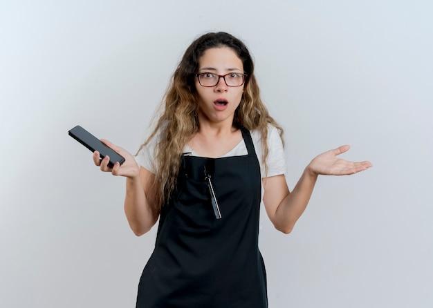 Junge professionelle friseurfrau in der schürze, die das smartphone betrachtet, das die vorderen achselzuckenschultern betrachtet, die verwirrt und unzufrieden sind, die über weiße wand stehen