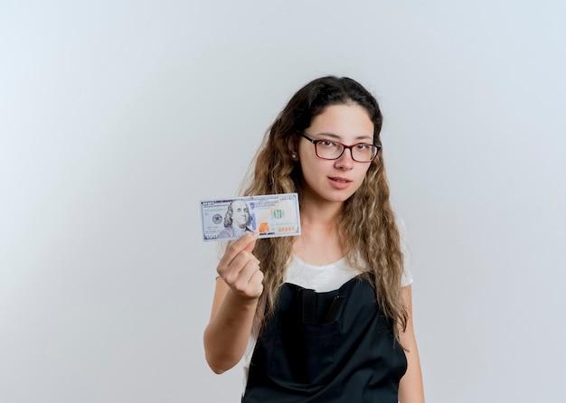 Junge professionelle friseurfrau in der schürze, die geld zeigt, das vorne mit ernstem gesicht steht, das über weißer wand steht