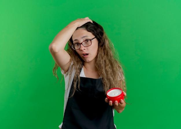 Junge professionelle friseurfrau in der schürze, die glas der haarcreme hält, verwechselt mit hand auf ihrem kopf für fehler