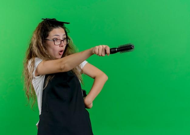 Junge professionelle friseurfrau in der schürze, die haarbürsten hält, die auf etwas zeigen, das überrascht ist, über grüner wand zu stehen