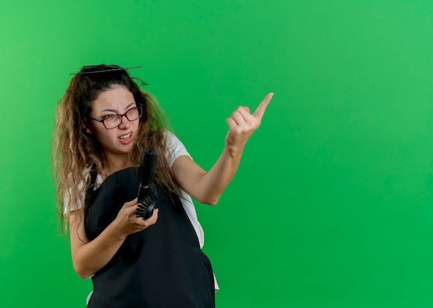 Junge professionelle friseurfrau in der schürze, die haarbürsten hält, die beiseite schauen und mit dem zeigefinger auf etwas zeigen, das unzufrieden ist, das über grüner wand steht