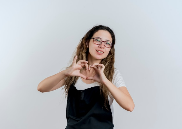 Junge professionelle friseurfrau in der schürze, die herzgeste mit den lächelnden fingern macht, die über weißer wand stehen