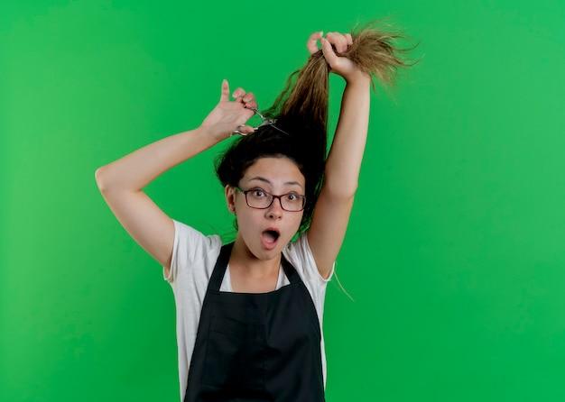 Junge professionelle friseurfrau in der schürze, die ihr haar bürstet und tut, das erstaunt ist, über grüner wand stehend