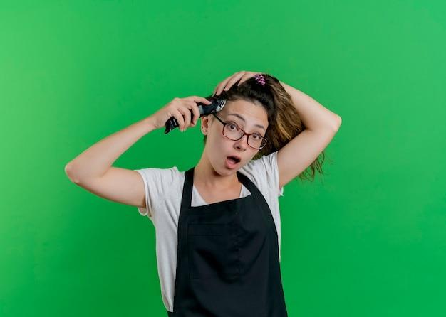 Junge professionelle friseurfrau in der schürze, die ihr haar mit trimmer schneidet, der vorne betrachtet wird, überrascht, über grüner wand stehend