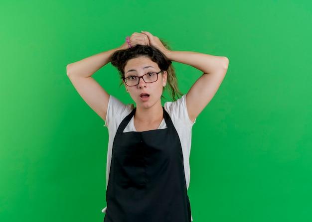 Junge professionelle friseurfrau in der schürze, die ihr haar tut, das vorne verwirrt steht und über grüner wand steht