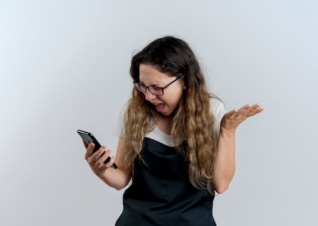 Junge professionelle friseurfrau in der schürze, die ihren smartphone-bildschirm betrachtet, der wild schreit, mit aggressivem ausdruck, der über weißer wand steht