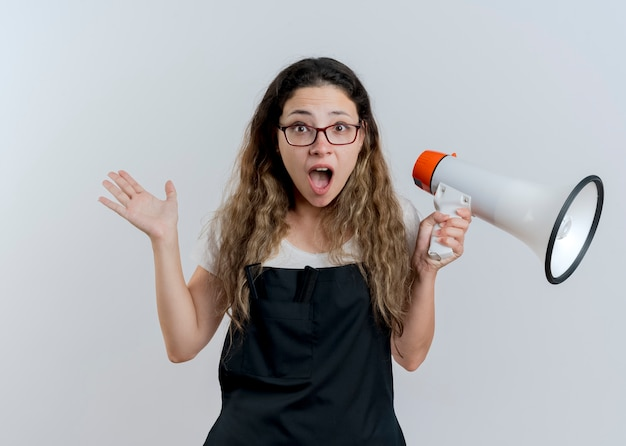 Junge professionelle friseurfrau in der schürze, die megaphon hält, das an der front schreit und verwirrt steht, über weißer wand stehend