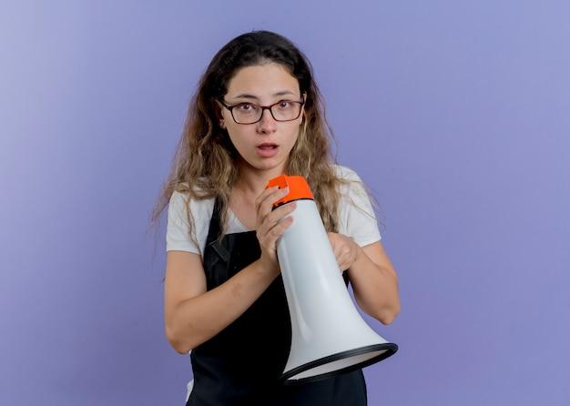 Junge professionelle friseurfrau in der schürze, die megaphon hält, das vorne verwirrt steht, das über blauer wand steht