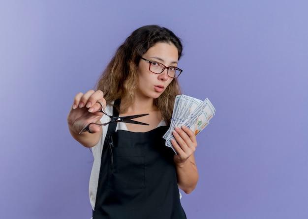Junge professionelle friseurfrau in der schürze, die schere hält, die bargeld zeigt, das zuversichtlich lächelt