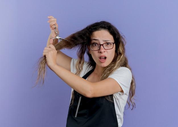 Junge professionelle friseurfrau in der schürze, die schere hält, die ihr haar schneidet, das verwirrt schaut
