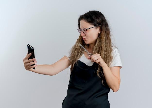 Junge professionelle friseurfrau in der schürze, die schere hält, die ihren smartphone-bildschirm betrachtet, der über weißer wand unzufrieden steht