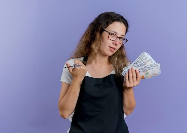 Junge professionelle friseurfrau in der schürze, die schere und bargeld mit lächeln auf gesicht hält