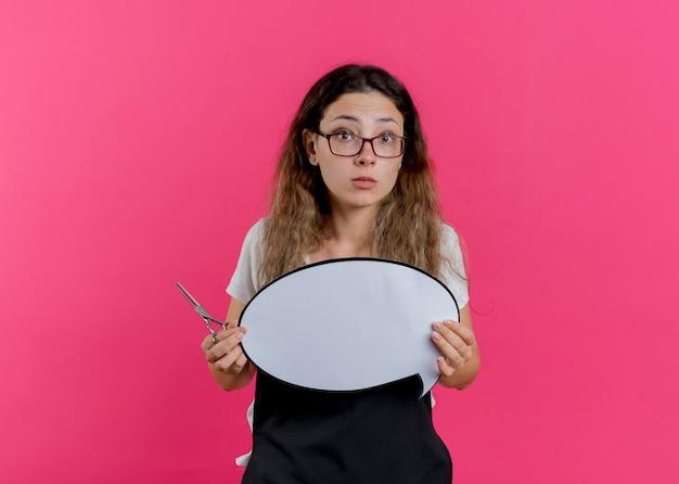 Junge professionelle friseurfrau in der schürze, die schere und leeres sprachblasenzeichen hält, das vorne betrachtet wird, das über rosa wand steht