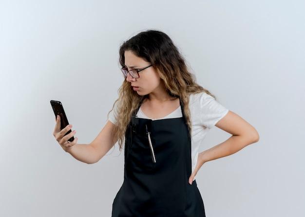 Junge professionelle friseurfrau in der schürze, die smartphone hält, das verwirrtes und unzufriedenes betrachten des bildschirms über weißer wand betrachtet
