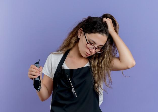 Junge professionelle friseurfrau in der schürze, die trimmer hält, der ihr haar mit traurigem ausdruck berührt