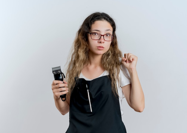 Junge professionelle friseurfrau in der schürze, die trimmer hält, der vorne mit ernstem gesicht betrachtet, das faust fasst, die über weißer wand steht