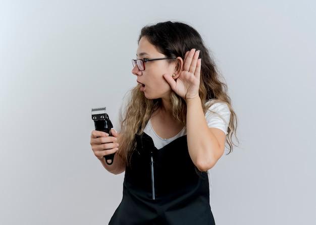 Junge professionelle friseurfrau in der schürze, die trimmer hält, die hand nahe ihrem ohr hält, das versucht, klatsch zu hören, der über weißer wand steht