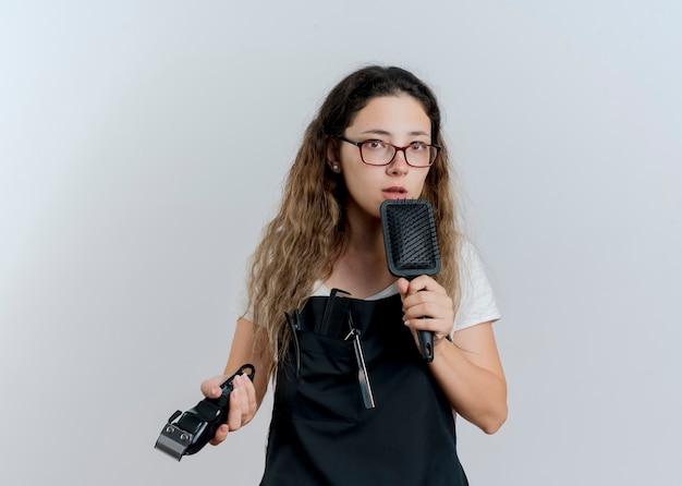 Junge professionelle friseurfrau in der schürze, die trimmer und haarbürste hält, die vorne mit ernstem gesicht über weißer wand steht