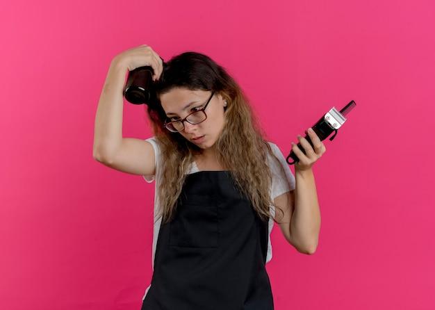 Junge professionelle friseurfrau in der schürze, die trimmerkamm und -spray hält, das verwirrt beiseite schaut