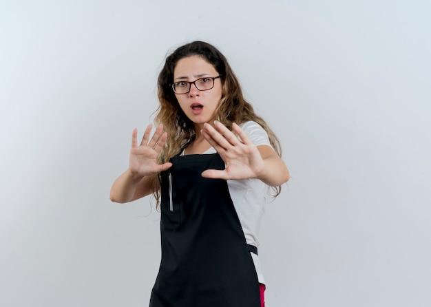 Junge professionelle friseurfrau in der schürze, die verteidigungsgeste mit den händen macht, die über weiße wand stehen stehen