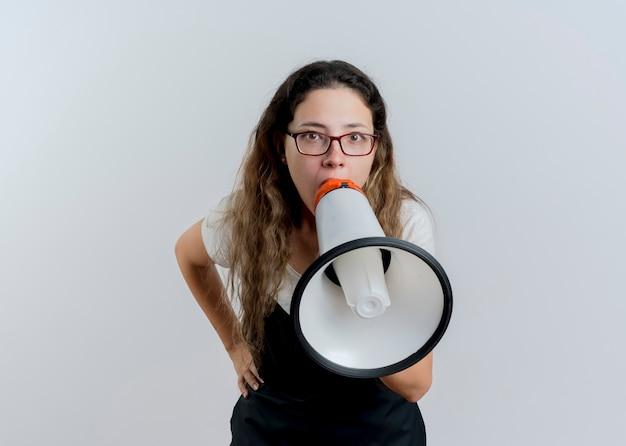 Junge professionelle friseurfrau in der schürze, die zum megaphon schreit, das laut über weißer wand steht