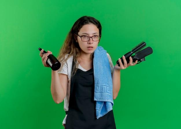 Junge professionelle friseurfrau in der schürze mit handtuch auf schulter, die haarbürsten und spray hält, das mit ernstem gesicht beiseite schaut