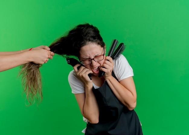 Junge professionelle friseurin in der schürze, die haarbürsten hält, die paing fühlen, weil jemand ihr haar zieht