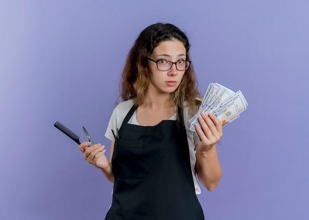 Junge professionelle friseurin in der schürze hält haarkamm, schere und bargeld verwirrt