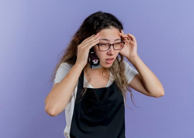 Junge professionelle friseurin in der schürze hält trimmer, der beiseite schaut, verwirrt und unzufrieden