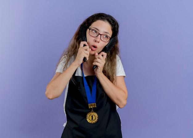 Junge professionelle friseurin in der schürze mit goldmedaille um den hals, die haarbürsten hält, die verwirrt beiseite schauen