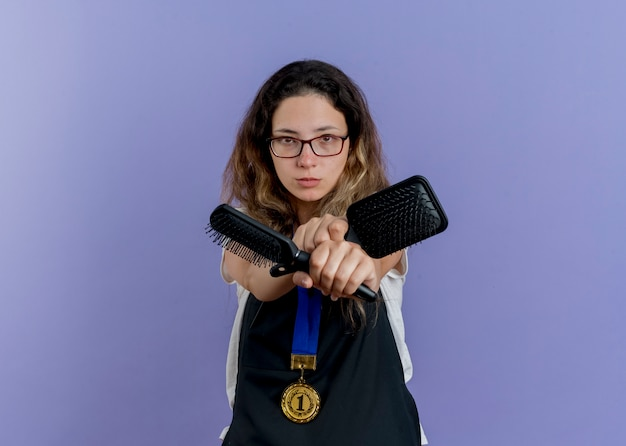 Junge professionelle friseurin in der schürze mit goldmedaille um den hals, die haarbürsten hält, die vorne mit ernstem gesicht kreuzende hände stehen über blauer wand stehen