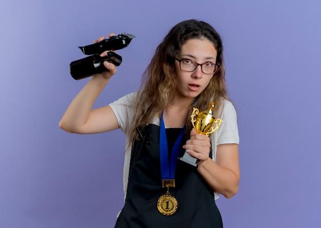 Junge professionelle friseurin in der schürze mit goldmedaille um den hals hält trimmer und trophäe, die vorne besorgt über blaue wand stehen