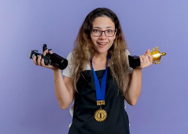 Junge professionelle friseurin in der schürze mit goldmedaille um den hals hält trimmer und trophäe lächelnd mit glücklichem gesicht