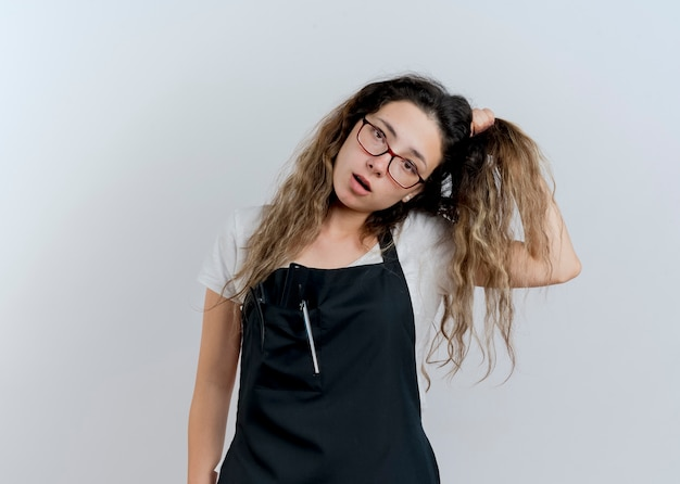 Junge professionelle friseurin in der schürze verwirrt, ihr haar berührend