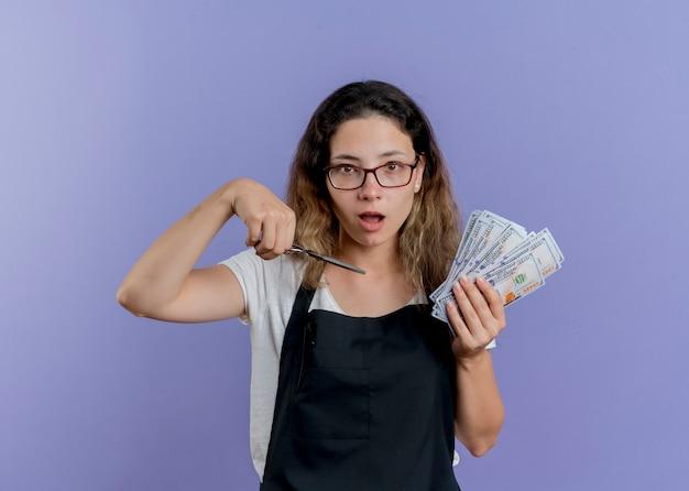 Junge professionelle friseurin in schürze mit schere und bargeld überrascht und erstaunt