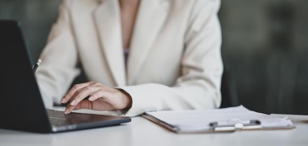Junge professionelle geschäftsfrau, die an ihrem projekt beim schreiben auf laptop arbeitet