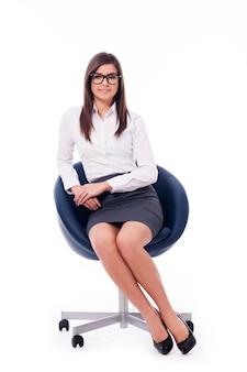Junge professionelle geschäftsfrau, die auf einem stuhl sitzt