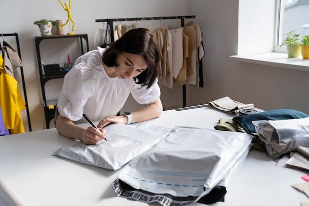 Junge professionelle schneiderin geschäftsfrau tippen kleidung für die lieferung an den kunden des ateliers verpackt