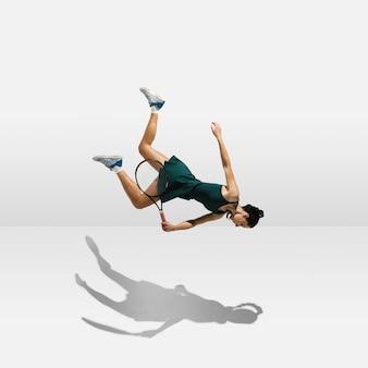Junge professionelle sportlerin, die das fliegen schwebt, während sie tennis spielt, isoliert auf weißer wand