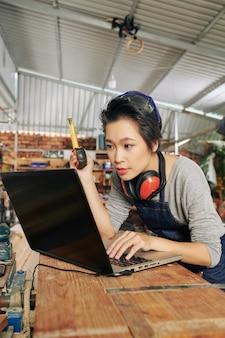 Junge professionelle tischlerin mit laptop, die abmessungen des möbelstücks prüft, das sie am arbeitsplatz machen wird
