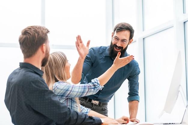 Junge profis geben sich gegenseitig eine hohe fünf. das konzept der teamarbeit