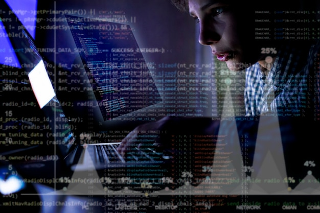 Junge programmierer vor dem laptop schreiben einen code in der nacht