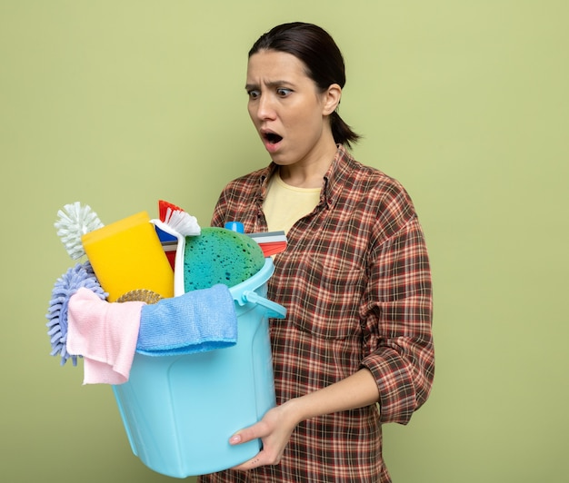 Junge putzfrau im karierten hemd, die eimer mit reinigungswerkzeugen hält, die erstaunt und schockiert auf grün beiseite schaut
