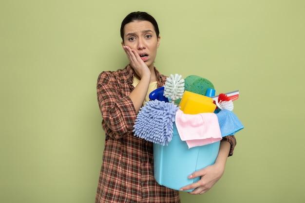 Junge putzfrau im karierten hemd, die eimer mit reinigungswerkzeugen hält, die nach vorne schauen, überrascht, über grüner wand zu stehen?