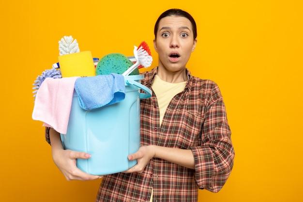 Junge putzfrau im karierten hemd, die eimer mit reinigungswerkzeugen hält, überrascht, dass sie auf orange steht