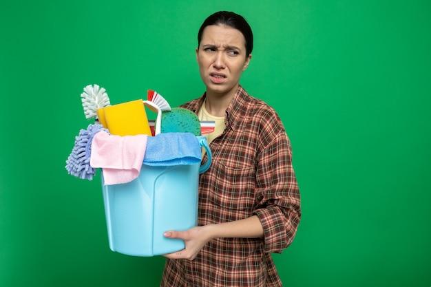 Junge putzfrau im karierten hemd, die eimer mit reinigungswerkzeugen hält und mit verwirrtem ausdruck auf grün beiseite schaut