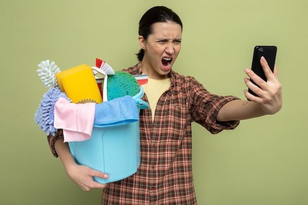 Junge putzfrau im karierten hemd, die eimer mit reinigungswerkzeugen hält und wütend und frustriert auf ihr handy schaut