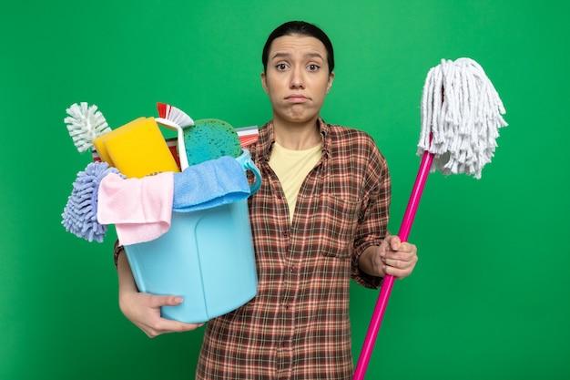Junge putzfrau im karierten hemd, die eimer mit reinigungswerkzeugen und mopp hält, verwirrt auf grün stehen