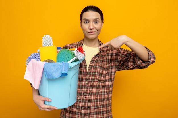 Junge putzfrau im karierten hemd, die einen eimer mit reinigungswerkzeugen hält, die mit dem zeigefinger auf sie zeigen und selbstbewusst stehend auf orange lächeln