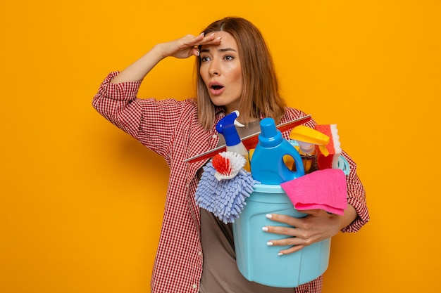 Junge putzfrau im karierten hemd, die einen eimer mit reinigungswerkzeugen hält, die mit der hand über den kopf weit wegschauen, um etwas oder jemanden zu suchen